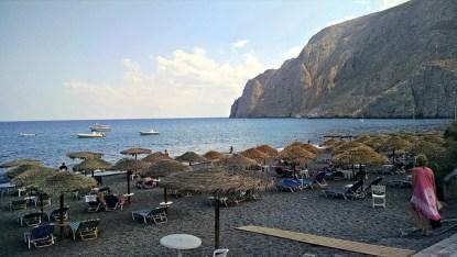 Sun beds, thatch umbrellas, warm ocean, beautiful cliffs.