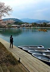 A boatman gazes out onto the Katsura River.