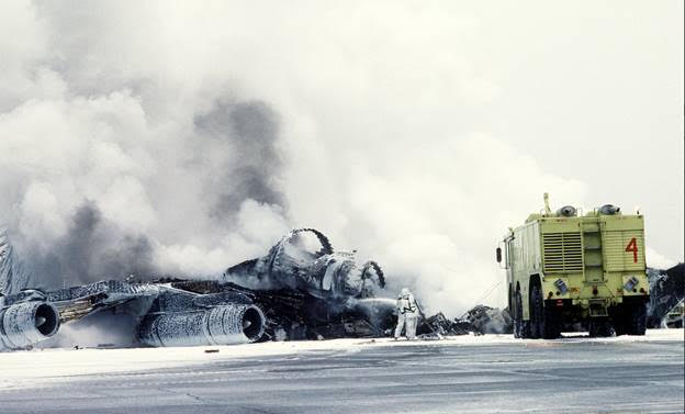 A crash crewman sprays a foam/water agent on an Alaska Air National Guard KC-135E Stratotanker aircraft that exploded and burned while taxiing to a parking area. Eielson AFB, Alaska