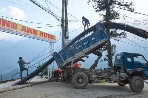 Men unload a truck full of steels used for hotel construction in Sa Pa.