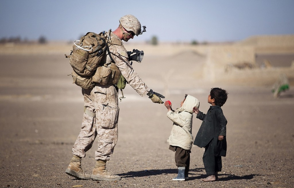 An American solider being greeted by local children.