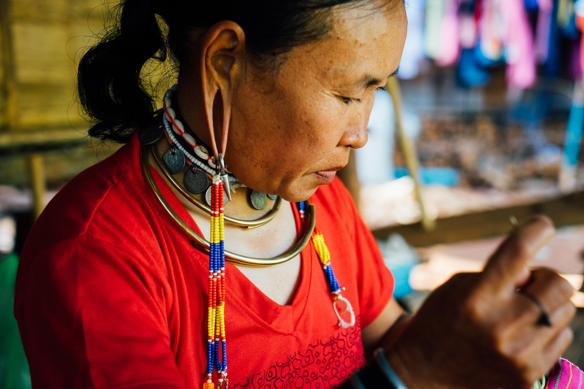 Thai woman threading beads in the traditional artisan way.