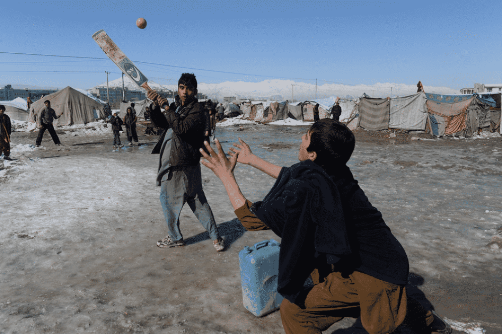 Internally Displaced Afghan Children Play Cricket In A Refugee Camp