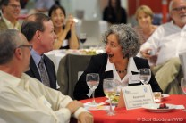 A woman leans across the table to look at the man to her right, her mouth wide open in surprise