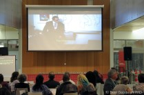 A crowd stares up at the movie playing on a large, projector screen