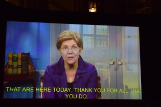 A video of Elizabeth Warren with yellow captions on the bottom