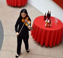 A young girl plays her violin and walksa round round tables in red tablecloths