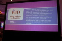 A large screen displays a slide about the Conference Accessibility Initiative