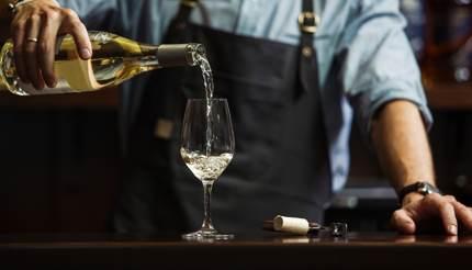 Bartender serving white wine