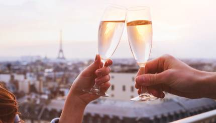 Two people clinking glasses of champagne or wine