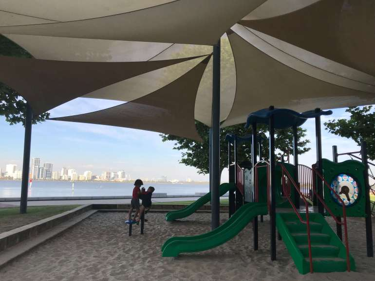 Playing at Mends St Jetty Playground with views of Perth City in the background