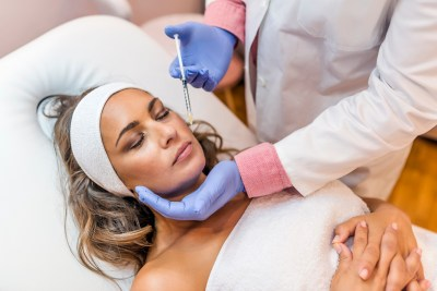 Photo of doctor cosmetologist makes Lip augmentation procedure of a beautiful woman in a beauty salon.Cosmetology skin care. Close up of hands of cosmetologist making Botox injection in female lips. He is holding syringe. Mature  beautiful Caucasian woman is receiving procedure with enjoyment.