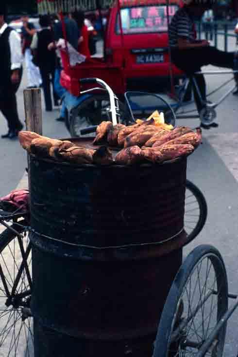 Sweet potatoes, popular street food in China, roast on a make-shift roaster.