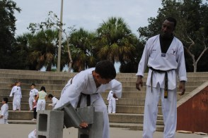 Breaking concrete for black belt test, age 12