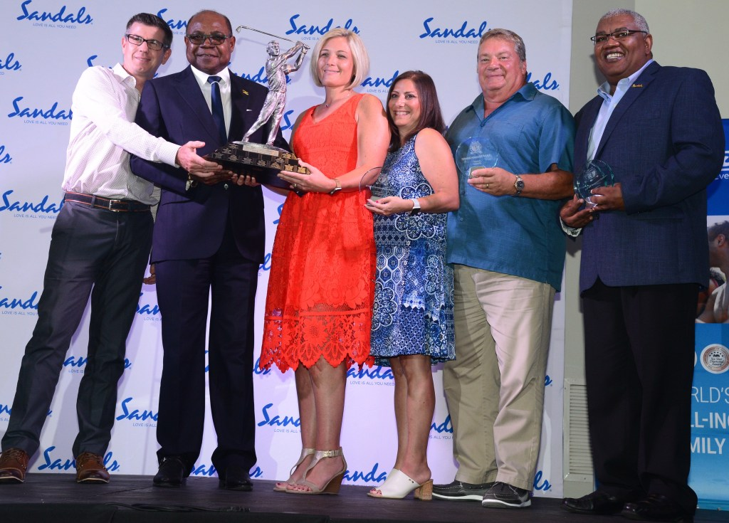 Minister of Tourism, Hon. Edmund Bartlett (2nd left) present the overall team winner's trophy to VIP travel agents (from left) Mark and Shayla Gerling, Doug and Jeanette Hernick at the Sandals 16th Annual USA Travel Agent Golf Tournament Awards Dinner at Sandals Ochi Beach Resort Saturday night, September 15, 2018. Sharing the occasion is Senior Vice President, Unique Vacations, Gary Sadler (right).