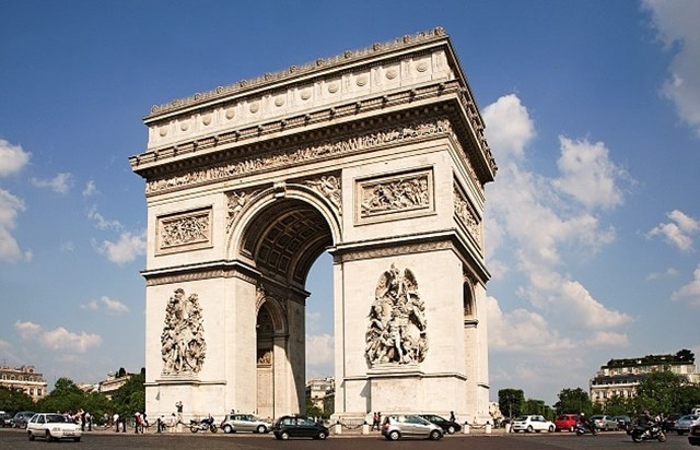 Arc de Triomphe on a sunny day. Lots of cars surround it