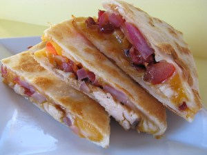 Three pieces of bacon chicken quesadilla on a white plate