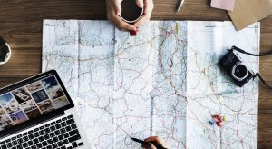 map with two people planning a trip, laptop, camera on the table and one person is cradling a cup of coffee