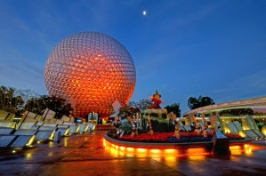Epcot at night. red light on ball like building. Mickey Mouse statue next to it.