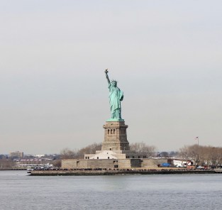 Statue of liberty reaching her arm high holding a torch