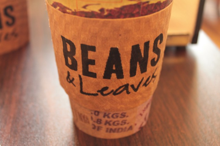 beige take out coffee cup with sleeve
