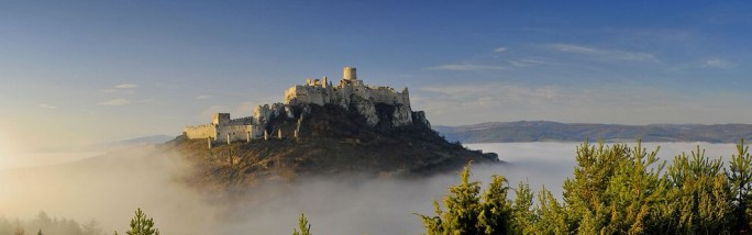 Spis castle on a hill with fog surrounding below in Slovakia