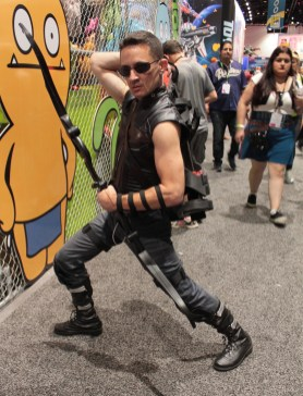 Hawkeye character reaches for his arrow as he stands in warrior pose