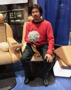 Star Trek space ship back ground as man dressed in red shirt and black pants holds a furry ball