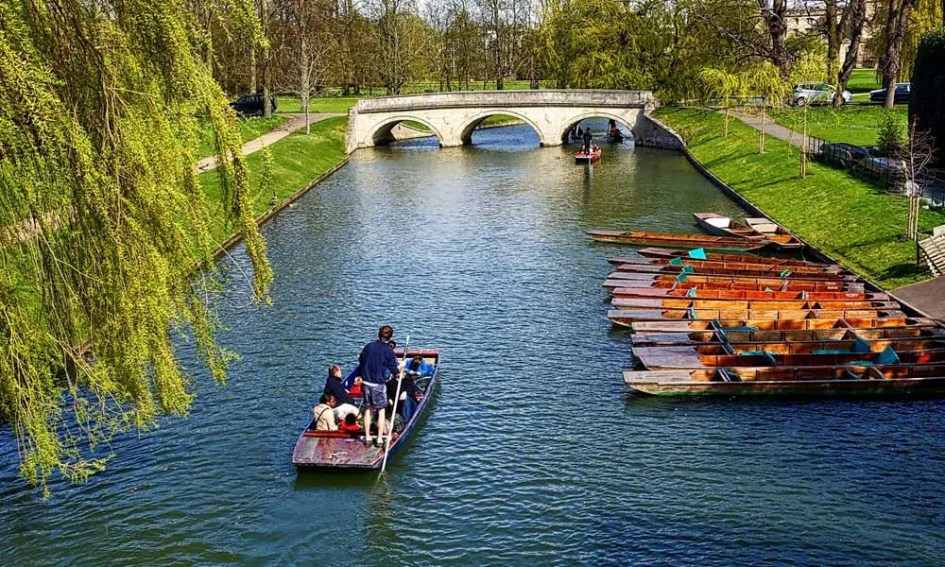 Depicts a group of friends on a boat on the Cambridge river