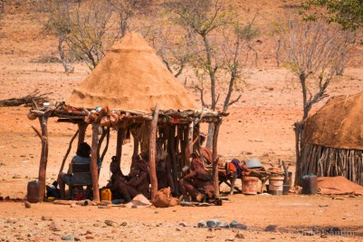 Himbas gathering in the shade given by their hut.