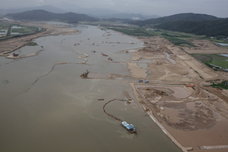 Aerial view of huge dredging and reclamation with mountains in the background