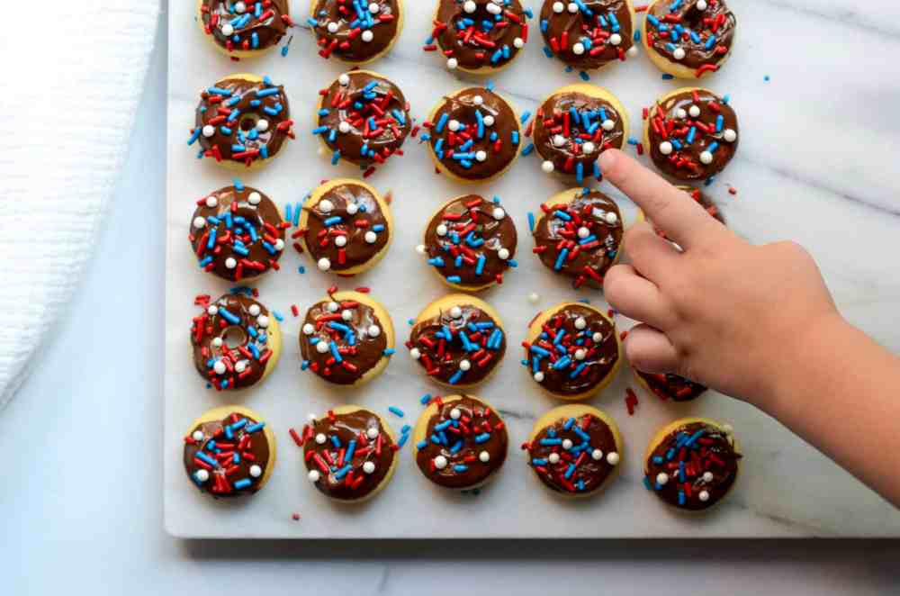 little hand touching mini baked donuts