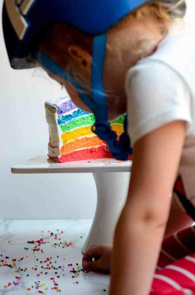 child with bicycle helmet blocking photo of rainbow cake