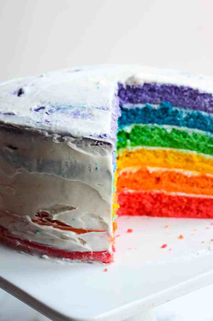 half frosted rainbow cake with colorful layers