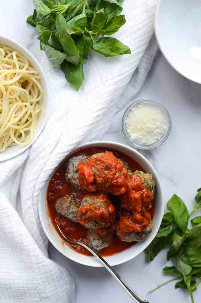 bowl of meatballs in marinara sauce with a bowl of spaghetti and fresh basil and parmesan