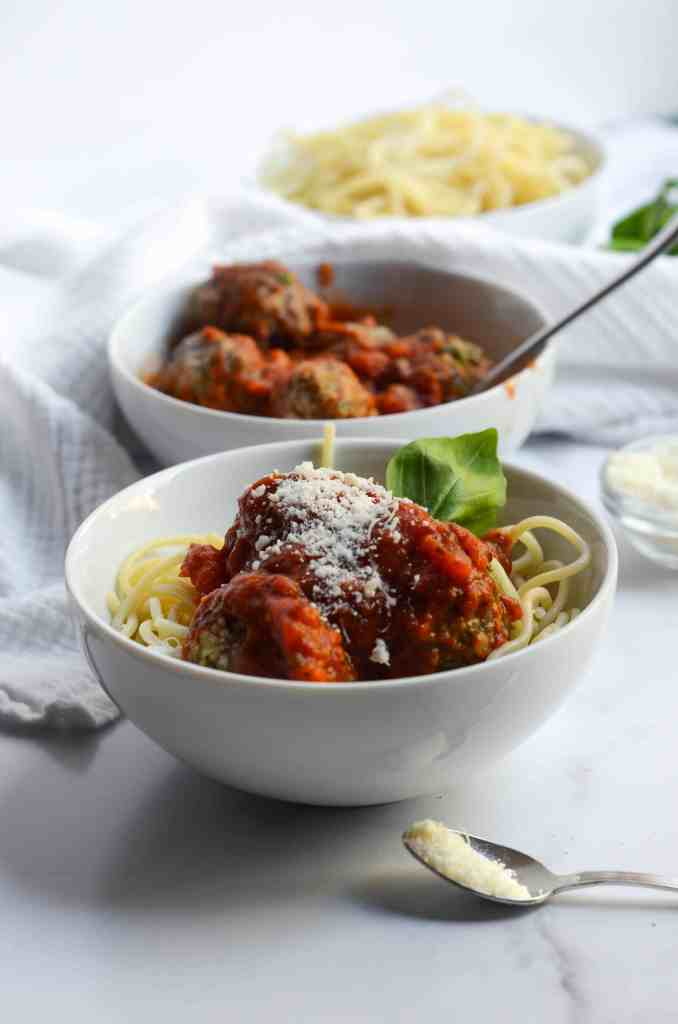 spaghetti and meatballs in a bowl with a bowl of meatballs and a bowl of spaghetti behind.
