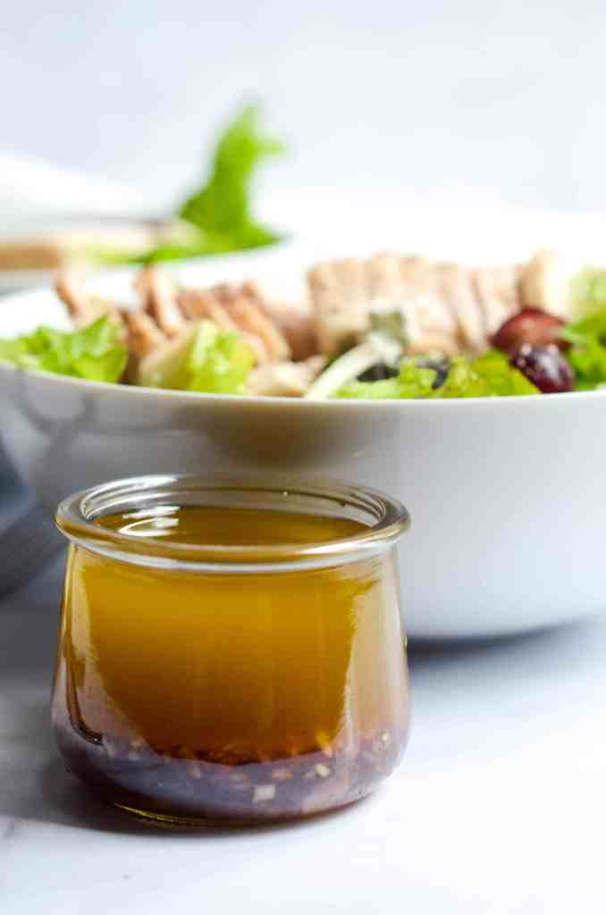 sherry vinaigrette in a jar with garlic and shallots falling to the bottom