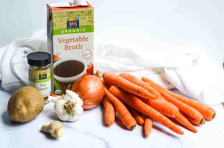 all 8 ingredients you need to make the vegan carrot ginger soup: carrots, potato, garlic, ginger, onion, bay leaves, and vegetable broth