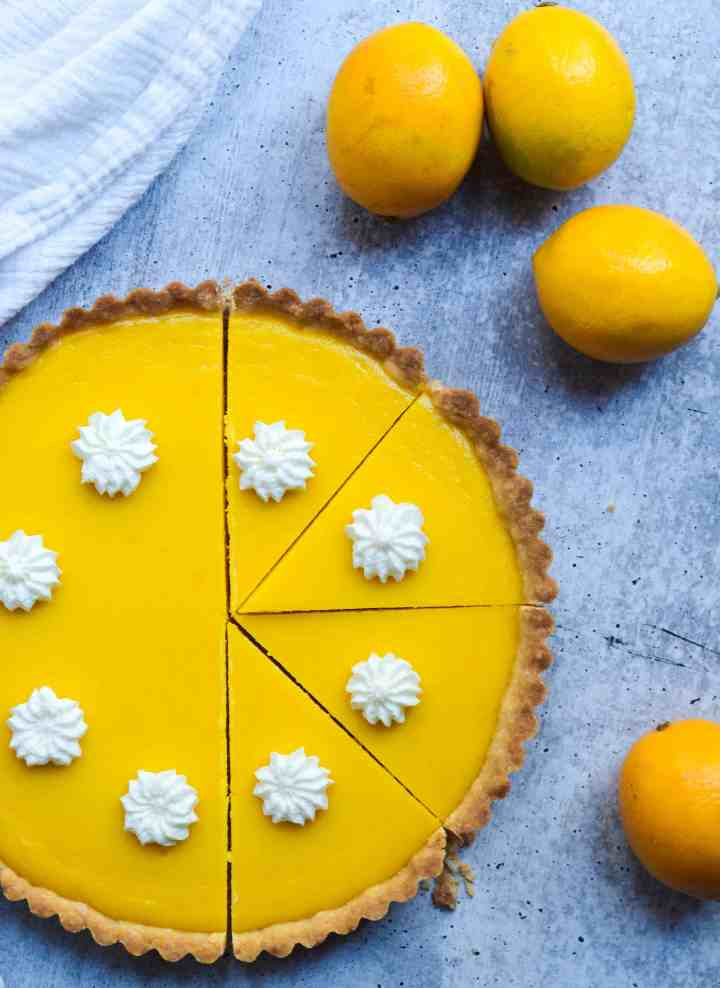 half cut meyer lemon curd tart topped with whipped cream and lemons around the tart.