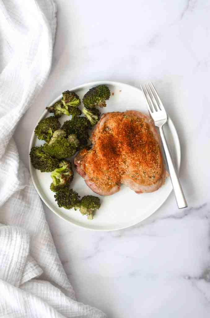 aerial view of baked and breaded pork chop with broccoli on white plate with white napkin