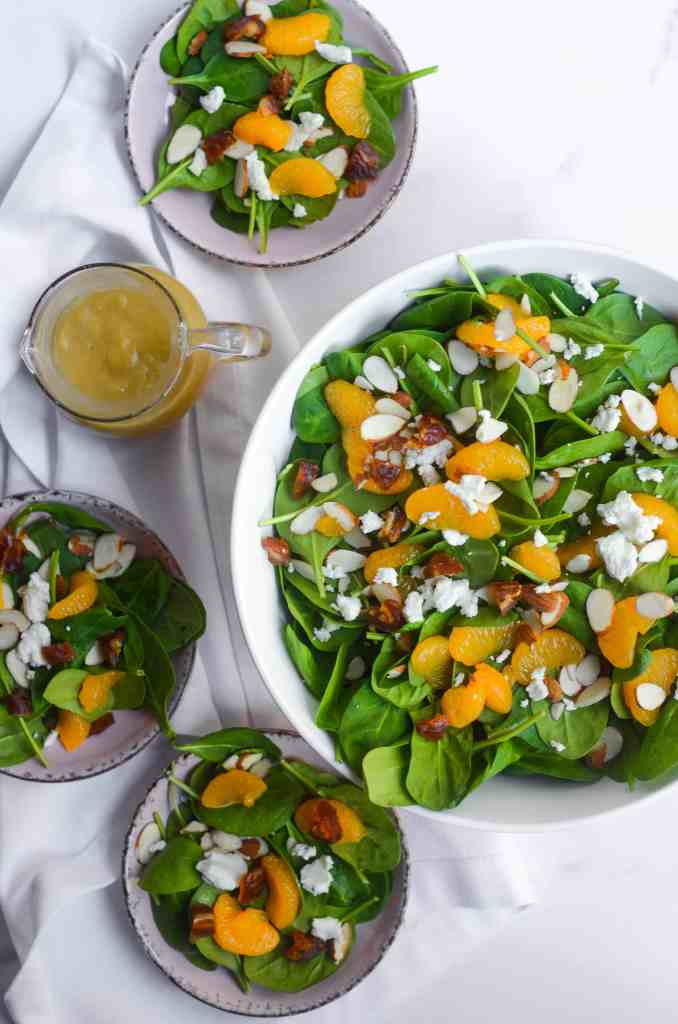 aerial view of large bowl of spinach salad with mandarin oranges, three smaller bowls of salad, and pour jar of vinaigrette.
