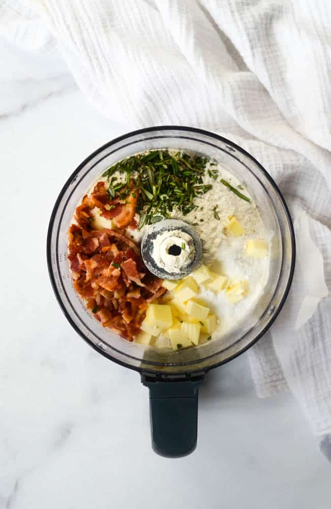 all ingredients needed to make rosemary and bacon biscuits in a food processor
