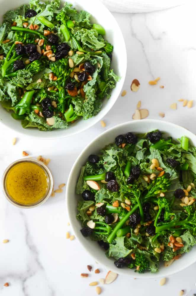 aerial shot of two bowls of kale salad with jar of vinaigrette and nuts scattered on the counter