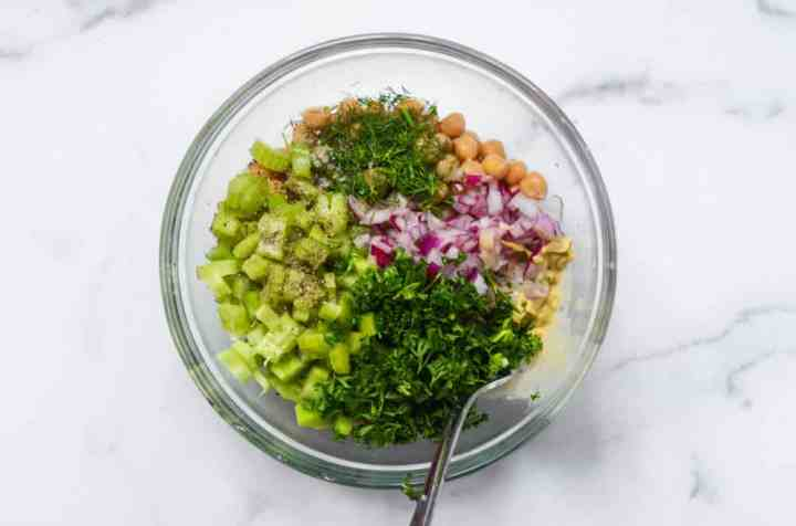 "aerial view of bowl with all of the ingredients to make chickpea ""chicken"" salad"