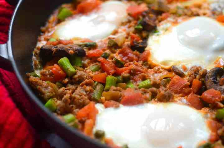 up close shot of vegetables and sausage in skillet with three poached eggs