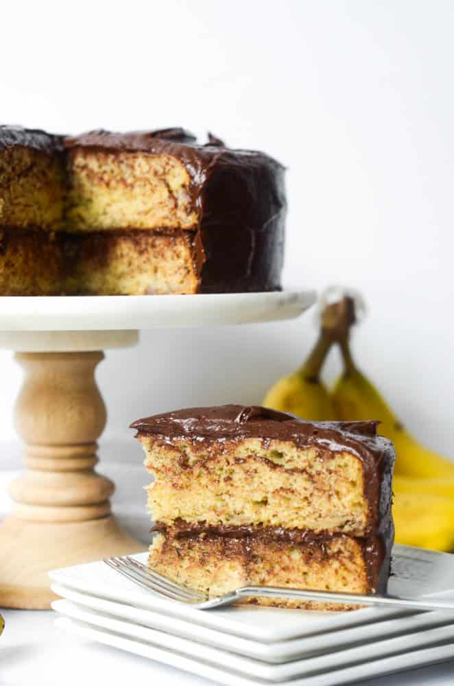 slice of banana cake on stack of white plates with rest of cake and bananas in the background