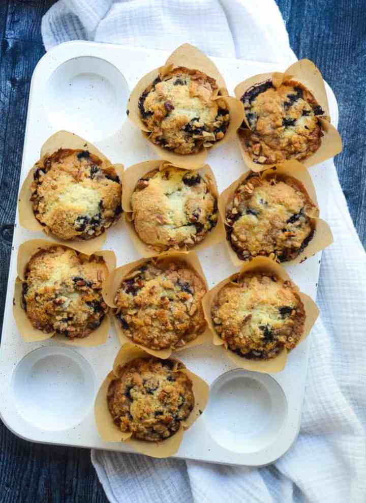 9 blueberry muffins sitting in white muffin tin on dark wood background