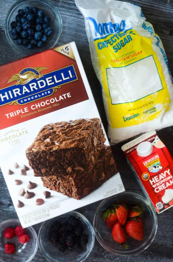 flat layout of ghirardelli brownie box, powdered sugar, heavy cream, strawberries, blackberries, raspberries and blueberries