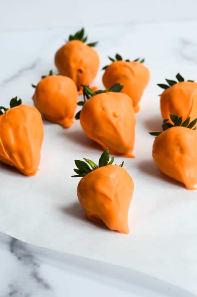 strawberries covered with orange candy melts on parchment paper