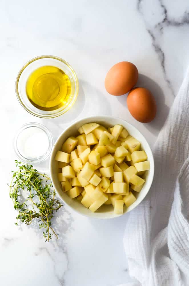 aerial shot of bowl of potatoes, thyme, salt, eggs, and olive oil